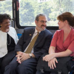 On his way to tour North Campus, President Schlissel ​shares a seat with VP Royster Harper and a faculty member ​on a blue bus