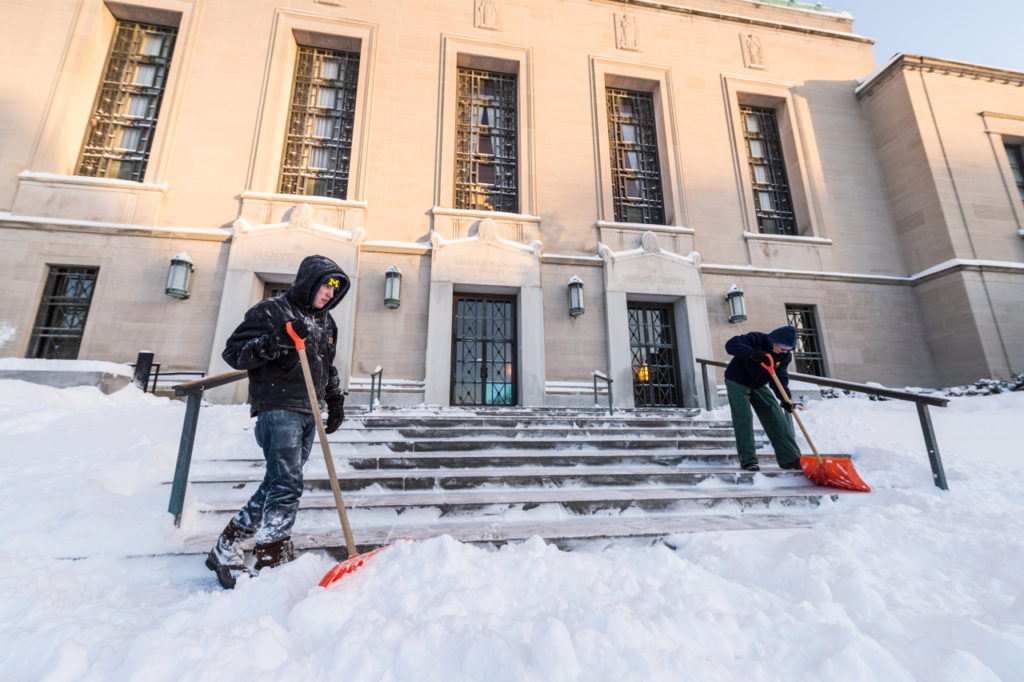 Tyler Douglas and Denise Schroeder shovel the stairs in front of Rackham