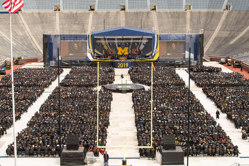 Wide view of 2019 spring commencement, looking over graduates toward the stage on the floor of Michigan Stadium.
