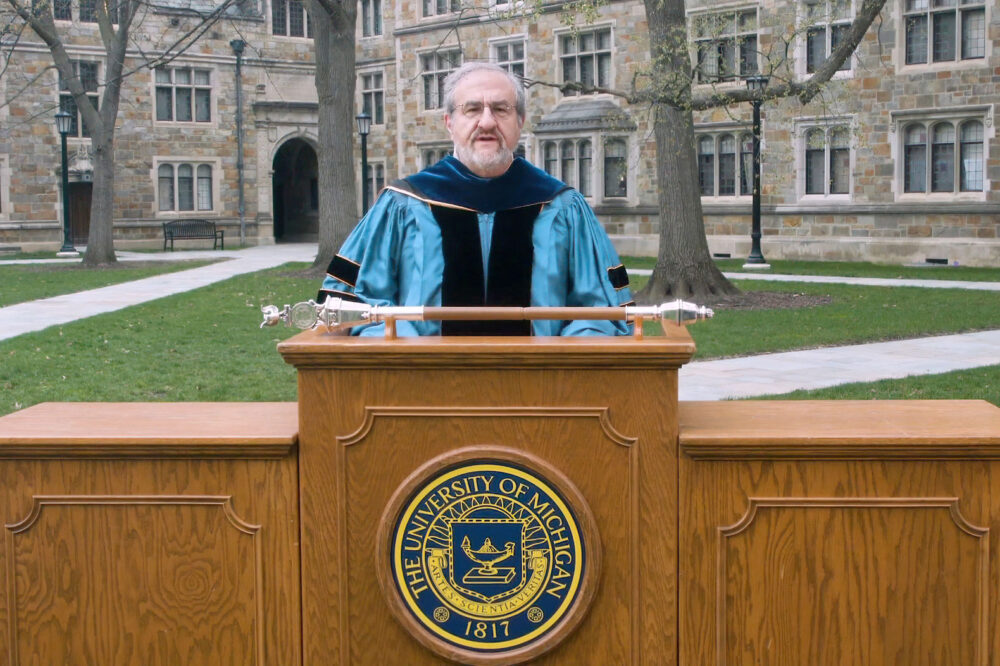 Mark S. Schlissel speaking at a podium on the Law Quad