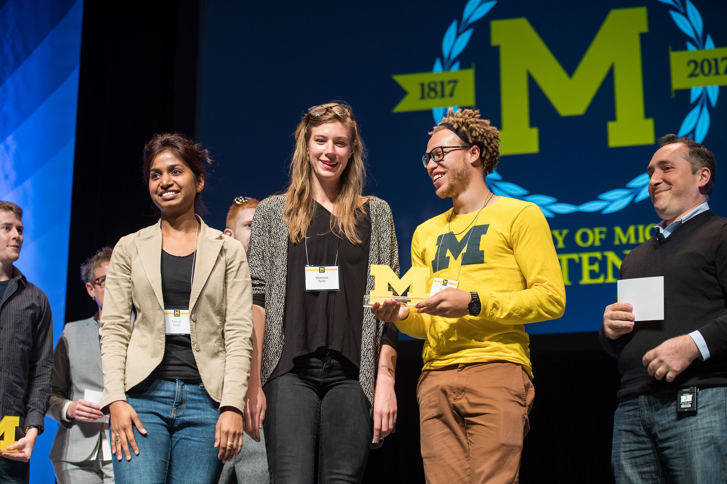 U-M alumnus and Amazon.com Vice President Babak Parviz, right, presents the 1st place design competition award to students, from left, Shruti Soni, Shannon Sylte and Derell Griffin, as part of the President Bicentennial Colloquium Campus of the Future.